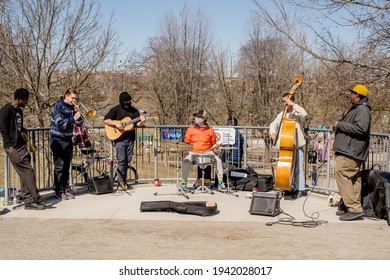 TORONTO, ONTARIO, CANADA - MARCH 18, 2021: MUSICIANS PLAY MUSIC AT CHRISTIE PITS PARK DURING COVID-19 PANDEMIC.
