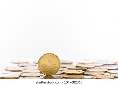 Toronto, Ontario / Canada - March 19, 2018: A pile of Canadian one dollar coins with one standing on top