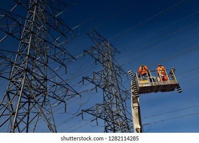 Toronto, Ontario, Canada - March 19, 2015: Hydro linemen on boom lift with old suspension insulators from high voltage power line towers