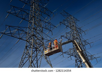 Toronto, Ontario, Canada - March 19, 2015: Hydro linemen on boom lift removing old suspension insulators on high voltage power line tower
