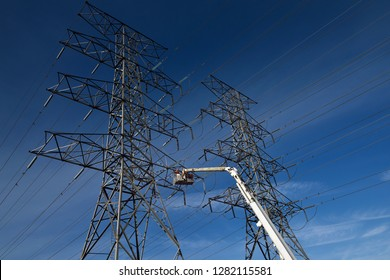 Toronto, Ontario, Canada - March 19, 2015: Hydro linemen working on replacing insulators on a double circuit high tension power line tower
