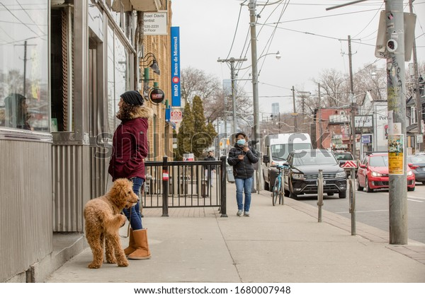 TORONTO, ONTARIO, CANADA - MARCH 21, 2020: WOMAN WITH DOG READS SIGN ON STORE WINDOW, WOMAN WEARING FACE MASKS WALKS BEHIND HER DURING CORONA VIRUS OUTBREAK.