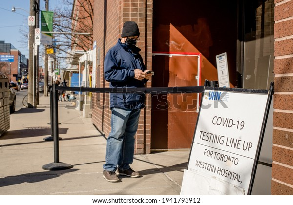 TORONTO, ONTARIO, CANADA - MARCH 21, 2021: Man waits in line for COVID-19 test at assessment centre.