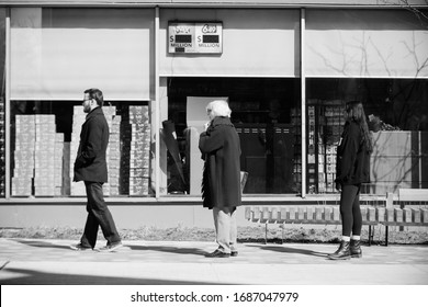 TORONTO, ONTARIO, CANADA - MARCH 28, 2020: PEOPLE PRACTICE 'SOCIAL DISTANCING' WHILE WAITING IN LINE TO ENTER GROCERY STORE. SOCIAL DISTANCING IS BEING ENFORCED DUE TO COVID-19 WORLDWIDE PANDEMIC.