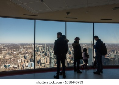 TORONTO, ONTARIO, CANADA - MARCH 4, 2018: PEOPLE AT THE CN TOWER, LOOKING AT CITY FROM OBSERVATION DECK.