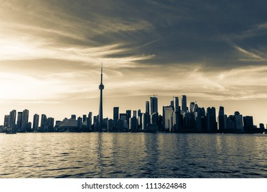 Toronto, Ontario, Canada, May 20, 2018, great amazing inviting natural landscape view of Toronto skyline, downtown area on dark golden sunset time at lake ontario, view from Center Island side