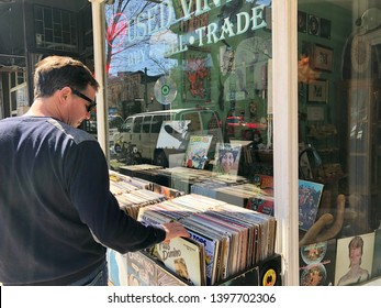 Toronto, Ontario / Canada - May 5, 2019: Man looking through vinyl record collection while sidewalk shopping on Queen Street East, Toronto,