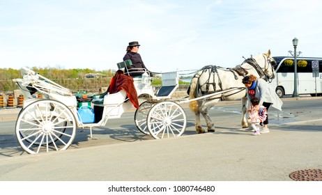 Toronto Ontario Canada. May 9th 2017. Mom was taking her child to take on the old or modern classic of carriage horse at Niagara falls. Concept of mom's day and vintage vehicle.