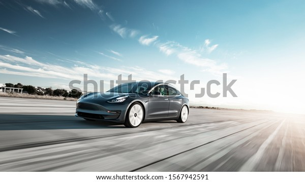 Toronto, Ontario / Canada - November 22nd 2019 : Photograph of a grey Tesla model 3 driving on the road with the sun setting in the background.