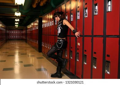 Toronto, Ontario, Canada - November 7, 2009: Sinister looking young female heavy metal punk rocker leaning on school lockers in a basement