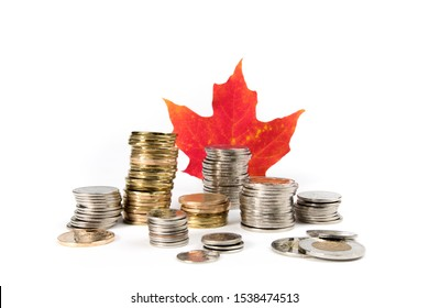 Toronto Ontario / Canada October 20 2019: rough stacks of Canadian dollar, quarter, dime and two dollar coins with a red maple leaf isolated on white