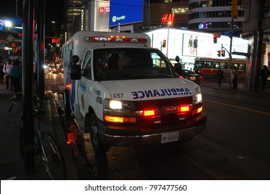 TORONTO, ONTARIO, CANADA - October 27 2017 - Ambulance on Yonge Street, city, 911, Emergency, car crash scene, Accident on the roads, injuries, paramedics with stretcher, flashing lights, aid, health