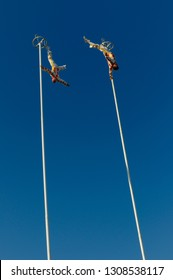 Toronto, Ontario, Canada - September 1, 2010: Two daredevil acrobates hanging upside down on top of 80 foot Thrill Poles