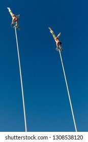 Toronto, Ontario, Canada - September 1, 2010: Two daredevil acrobates doing handstands on top of 80 foot Thrill Poles