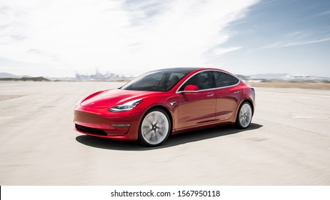Toronto, Ontario / Canada September 20th 2019 : Photograph of a red Tesla model 3 in front of a distant city.