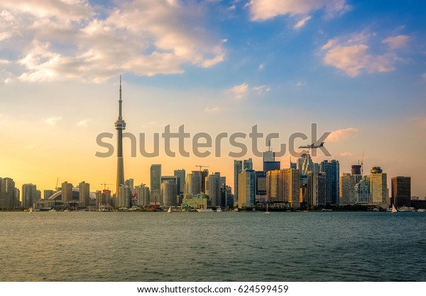 Toronto, Ontario, Canada -September14, 2012: Toronto City Skyline view from the inner Harbour at sunset. An airplane is fligh low preparing to land to the near-by airport.