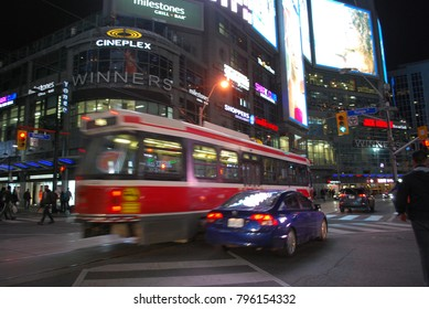 TORONTO, ONTARIO, CANADA - TTC Streetcar At Night At Dundas Square - Toronto City Public Transportation, Downtown, Tram, Evening in town with lights, Eaton Centre Mall, Traffic, Cars, Intersection