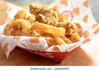 Toronto, Ontario, Canada-December 12, 2018: Popeyes real food: five chicken tenders with onion rings. The Popeyes restaurants are very popular in the metropolitan city
