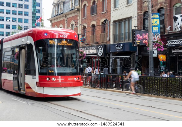 TORONTO, ONTARIO - July 24, 2019: TTC Streetcar in downtown Toronto's entertainment district with bicyclist passing by.