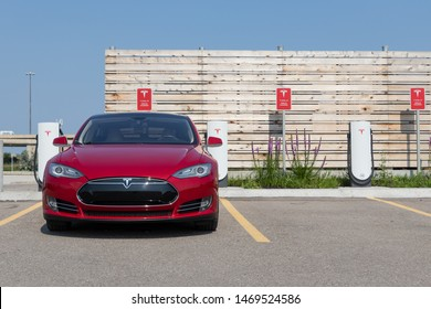 TORONTO, ONTARIO - July 26, 2019: Front of 2014 Red Tesla Model S while charging at Tesla Urban Supercharger.