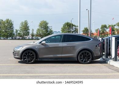 TORONTO, ONTARIO - July 26, 2019: Bronze Tesla Model X plugged-in, charging at Tesla Urban Supercharger.