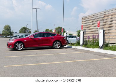 TORONTO, ONTARIO - July 26, 2019: Red Tesla Model S plugged-in, charging at Tesla Urban Supercharger with Model X and Model S in background.