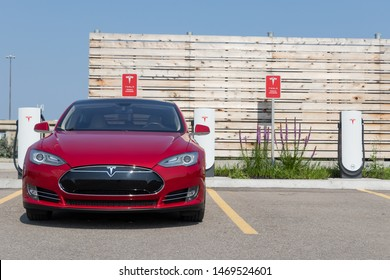 TORONTO, ONTARIO - July 26, 2019: Front of Red Tesla Model S while charging at Tesla Urban Supercharger.