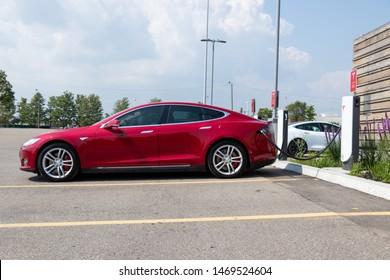 TORONTO, ONTARIO - July 26, 2019: Red Tesla Model S plugged-in, charging at Tesla Urban Supercharger.