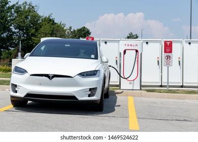 TORONTO, ONTARIO - July 26, 2019: Front of White Tesla Model X while recharging at Tesla Supercharger.