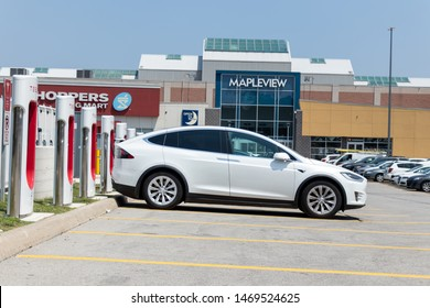 TORONTO, ONTARIO - July 26, 2019: White Tesla Model X parked at Tesla Supercharger recharging at Burlington Mapleview Mall.