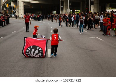 TORONTO, ONTARIO - June 17, 2019: A child wear a Toronto Raptors Kyle Lowry jersey holding a Toronto Raptors flag while running down the street.