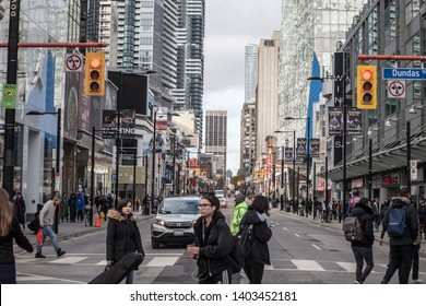 TORONTO, ONTARIO - NOVEMBER 13, 2018: Skyscrapers on Yonge street, on Yonge Dundas Square, with people crossing on a sidewalk, stores and shops, in a typical North American big city architecture