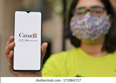 Toronto, Ontario,Canada, 2020. Girl wearing face mask showing Covid-19 app on mobile phone. Health Canada in partnership with Thrive Health has created the Canada COVID-19 app for controlling pandemic