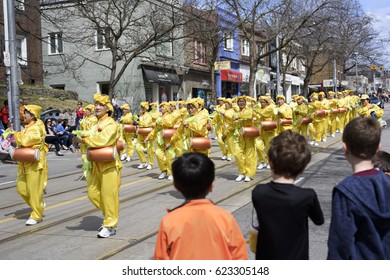 TORONTO, ONTARIO/CANADA - APR 16, 2017: Falun Dafa marching group dressed in traditional Chinese costume play waist drum during the Beaches Easter Parade 2017 on Queen Street East Toronto