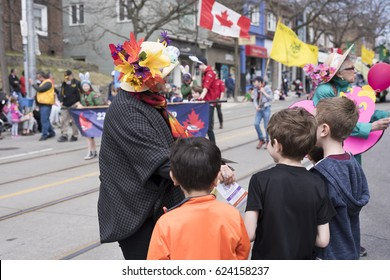 TORONTO, ONTARIO/CANADA - APR 16, 2017: woman in Easter costume distributes gifts to children along the Queen Street East in the Beaches Easter Parade 2017
