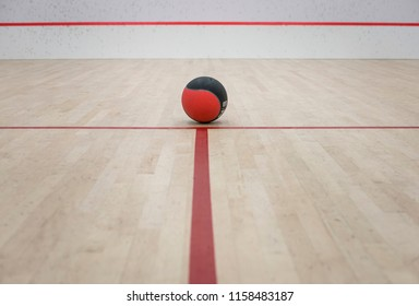 TORONTO, ONTARIO/CANADA - AUGUST 15, 2018: A red and black exercise ball in the middle of a squash court. Straight red line towards the ball. View from the front. Space for text or caption.