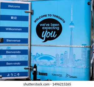 Toronto, Ontario/Canada - August 29 2019:     A blue information kiosk for tourists at Nathan Phillips Square shows pictures of the city skyline with welcome messages in a multitude of languages.