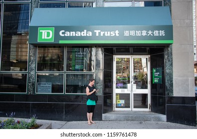 TORONTO, ONTARIO/CANADA - JULY 25, 2018: An unidentified woman outside of a Canada Trust bank branch, with Chinese calligraphy, located in the Chinatown section of downtown Toronto.