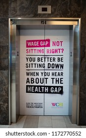 TORONTO, ONTARIO/CANADA - JULY 25, 2018: A photo of a political sign on an elevator at the Women's College in Toronto about health and wage gaps.