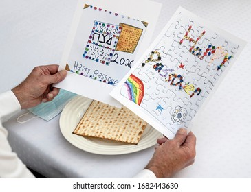 TORONTO, ONTARIO/CANADA-MARCH 21 2020: A grandfather reads greetings from his grandchildren  while social distancing at Passover during Coronavirus