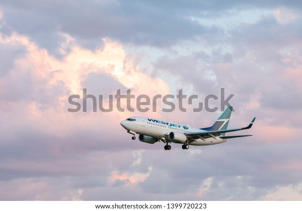 Toronto Pearson Airport, Canada - May 15 2019: close view of West Jet airlines Boeing 737-700 airplane landing / taking off from runway tarmac. Aircraft industry and air transport travel concept.