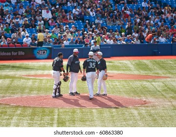 TORONTO - SEPT 11:  Blue Jays coach Cito Gaston consults with pitcher David Purcey, first baseman Lyle Overbay, and catcher Jose Molina against the Tampa Bay Rays, September 11, 2010 in Toronto.