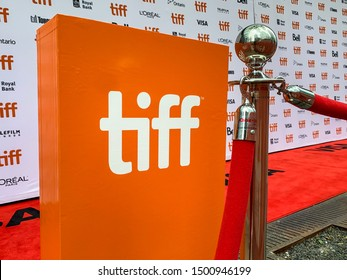 "Toronto - September 10, 2019: A sign displaying the ""TIFF"" logo stands guard on an  empty red carpet space awaiting the next slew  of celebrities to attend the the Toronto International Film Festival."