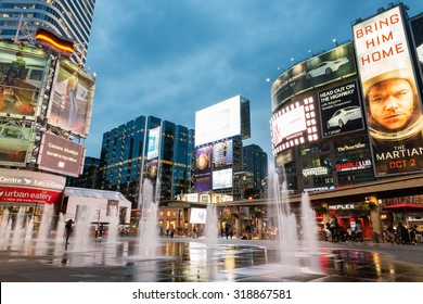 TORONTO - SEPTEMBER 12: People shop and relax at Yonge and Dundas Square in Toronto at dusk, illuminated by the lights of the colorful neon billboards and advertisement, on September 12, 2015.