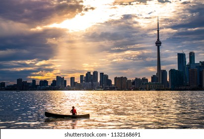 TORONTO SKYLINE - Canoe being paddled past Toronto skyline at sunset. Silhouetted canoer exploring outdoors in urban city setting. Rays of sunlight shining on Lake Ontario. Toronto, Ontario, Canada.
