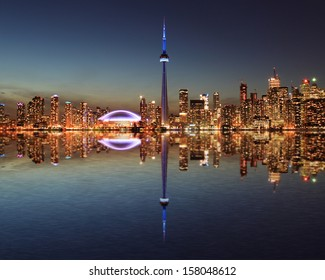 Toronto Skyline at night with a reflection in Lake Ontario.