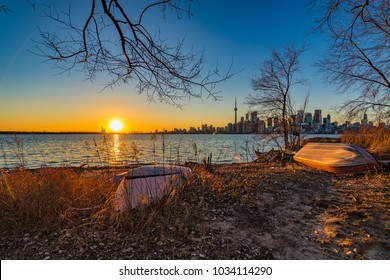 Toronto skyline silhouette at sunset from Ward´s Island beach with boats in the foreground.