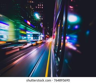 TORONTO STREETCAR SPEEDING THROUGH DOWNTOWN CITY AT NIGHT - Fast-motion public transit vehicle speeding down street core with beautiful color streaks. Train transportation. Toronto, Ontario, Canada