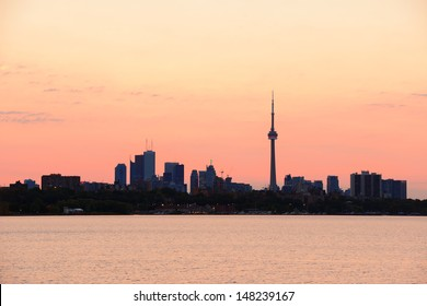 Toronto sunrise silhouette over lake with red tone.