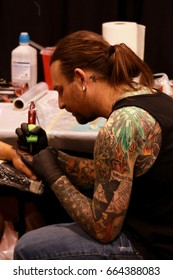 Toronto Tattoo Show: Northern Ink Xposure, June, 2017, Ontario, Canada. Tattoo convention, expo. Alternative style, rock attire, ink art. Tattoo master at work. Work in progress.